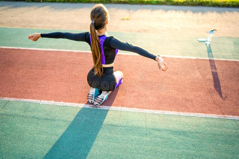 Girl sportsman crossfit and run at sunset in the stadium.  stock photography