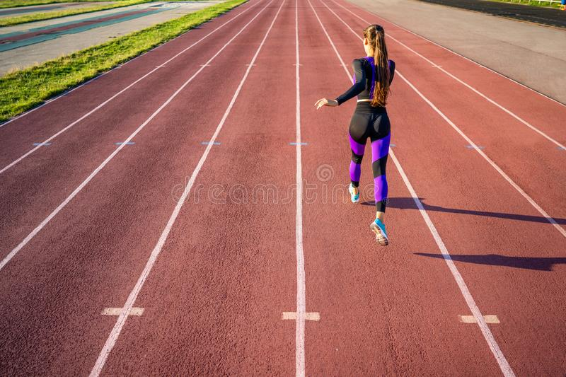 Girl sportsman crossfit and run at sunset in the stadium.  royalty free stock image