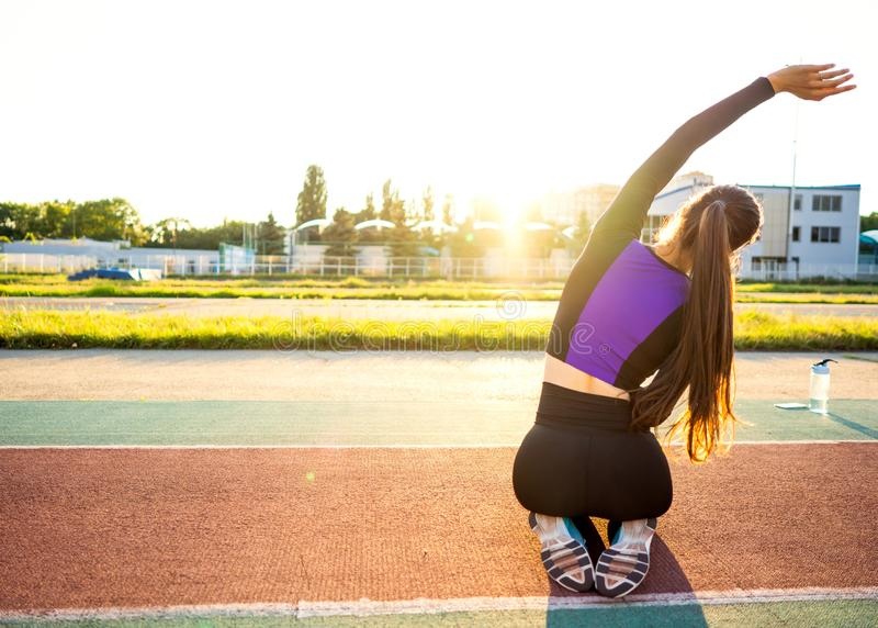 Girl sportsman crossfit and run at sunset in the stadium.  royalty free stock photography