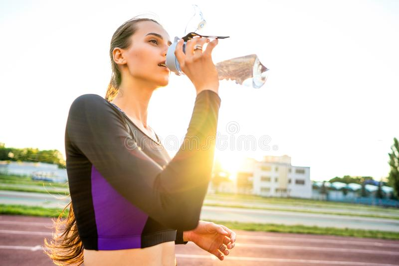 Girl sportsman crossfit and squats agains and drinks water at sunset royalty free stock images