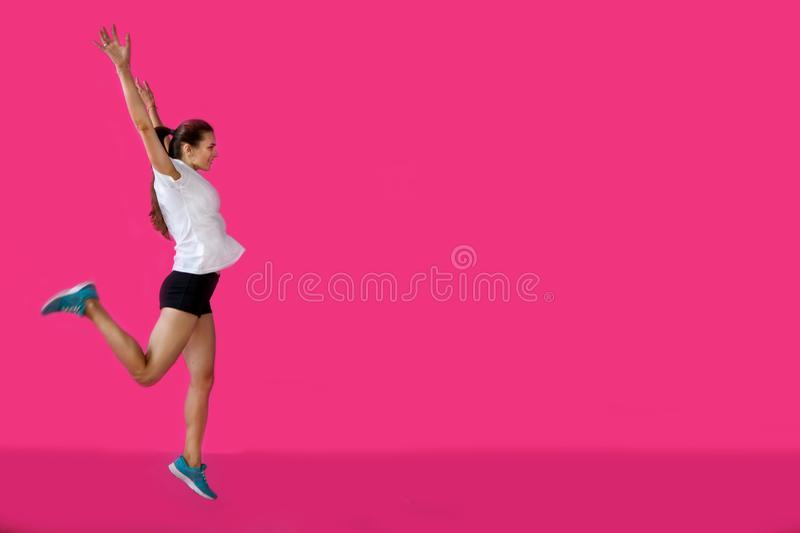 Girl sportsman posing on a pink background royalty free stock image