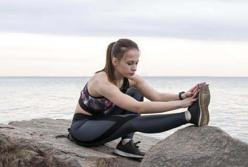 Girl in sportswear engaged in fitness on the stone on the seashore. 1 white girl in sportswear engaged in fitness on the stone on the seashore royalty free stock photos