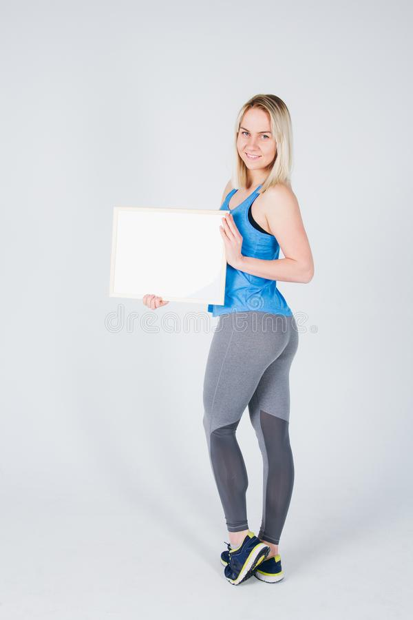 Girl in sportswear holding a frame with an ad royalty free stock photo