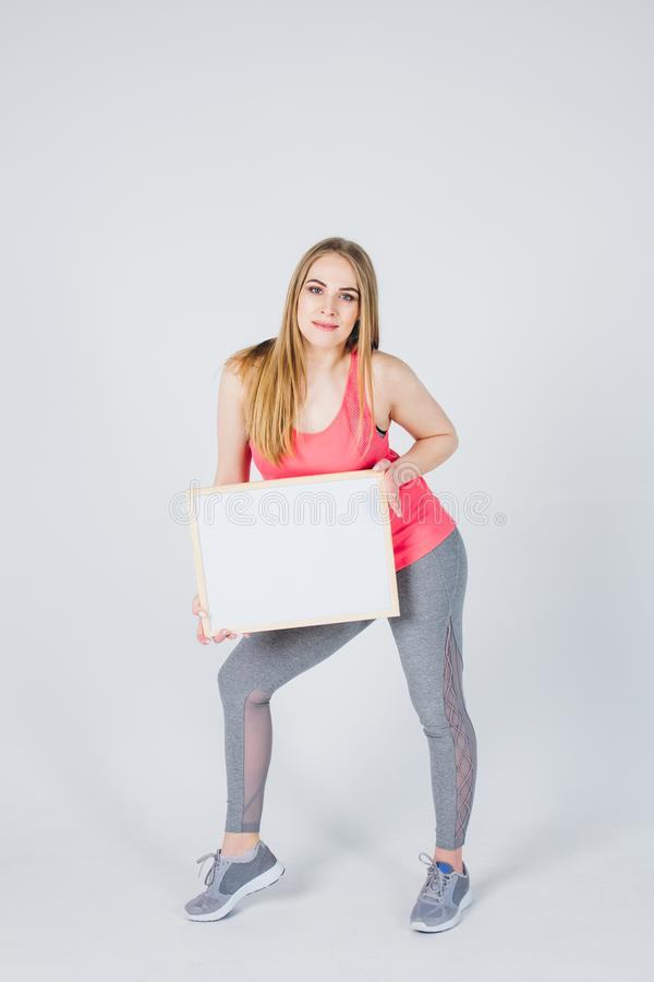 Girl in sportswear holding a frame with an ad stock photography