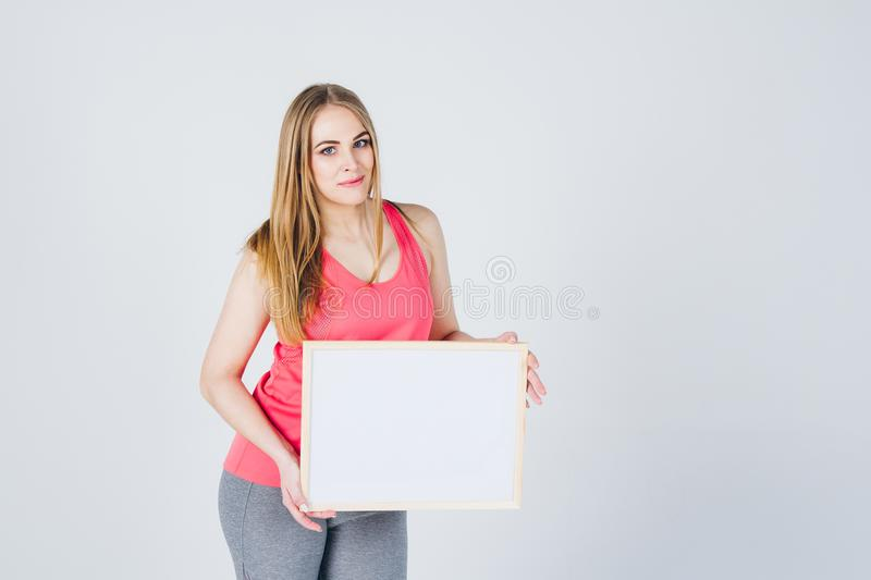 Girl in sportswear holding a frame with an ad royalty free stock image