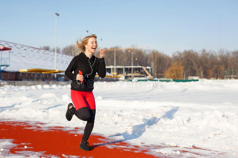Girl in sportswear run on the red track for running on a snow-covered stadium Fit and sport lifestyle. Run and listening music. stock photo