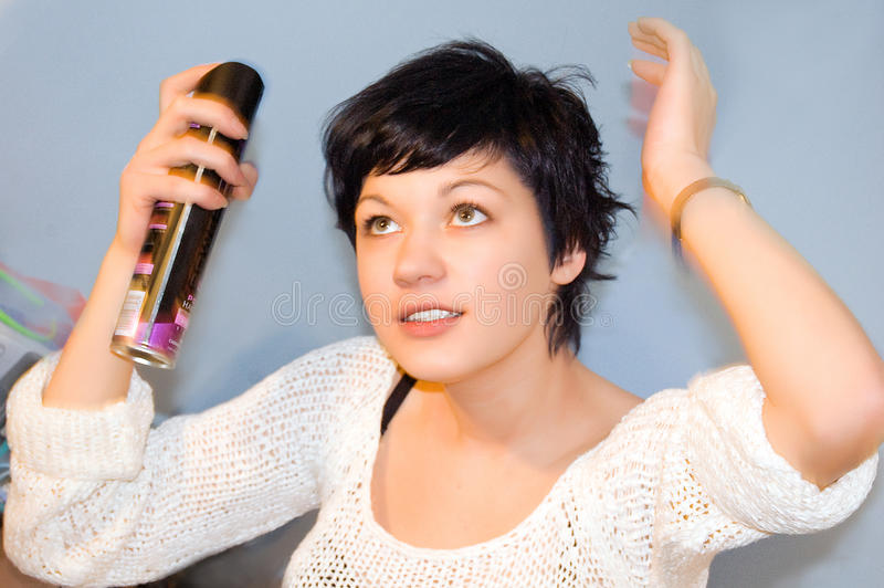 Girl spraying hair lacquer onto her hair. Shorthaired girl spraying hair lacquer onto her hair royalty free stock photo