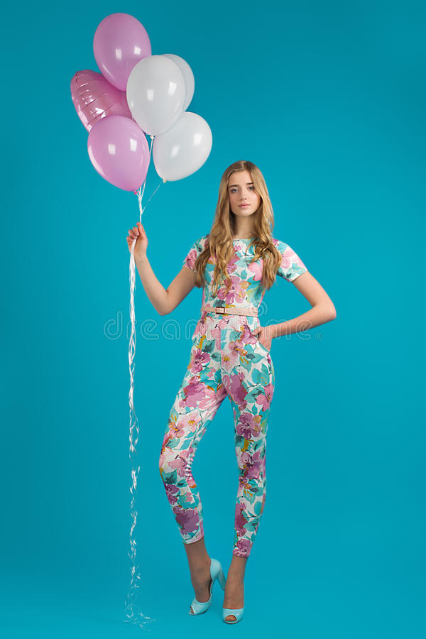 Girl in spring overalls with balloons, carefree mood stock image