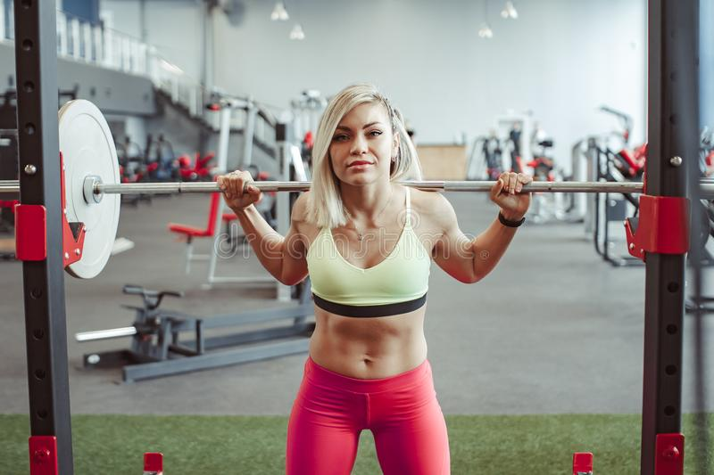 Girl squats with a barbell stock photo