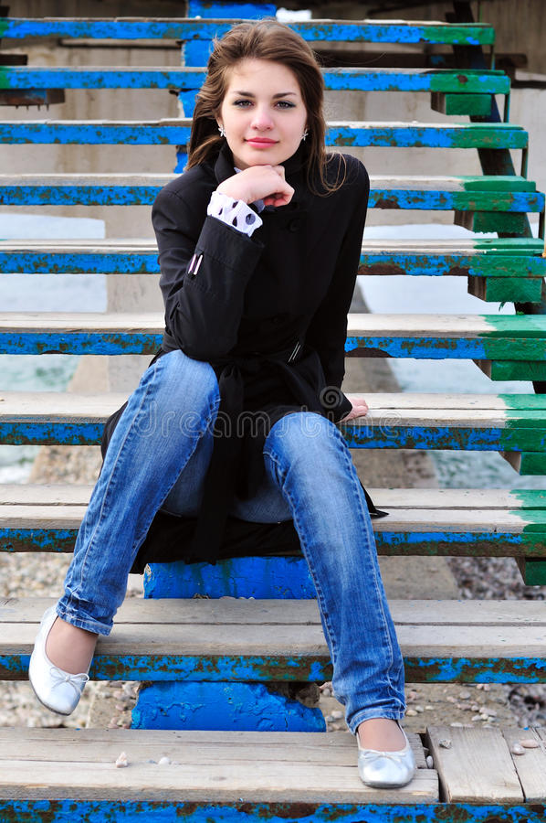 Girl on the stairs on the beach royalty free stock photography