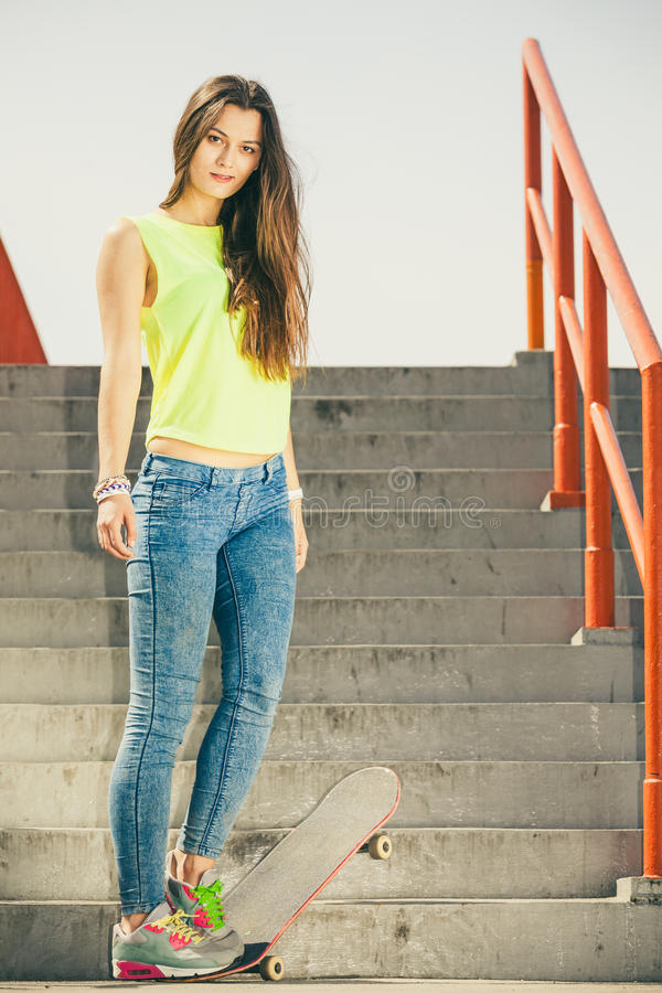 Girl on stairs with skateboard. Cool skate young long haired girl riding skateboard on the urban stairs. Active lifestyle funky in summer. Outdoor trendy sport stock image