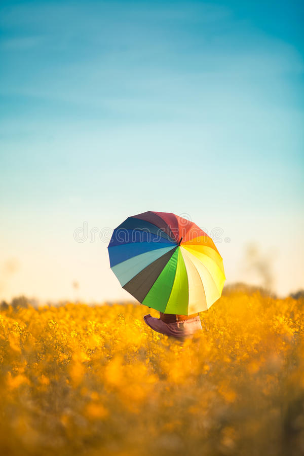 Girl stand with a colorful umbrella stock photography