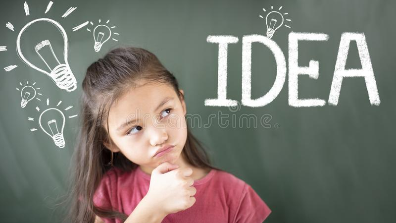 girl standing against chalkboard and idea bulb concept royalty free stock images