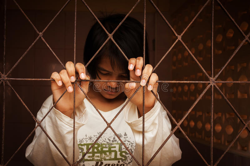 Girl standing alone behind jail royalty free stock photos