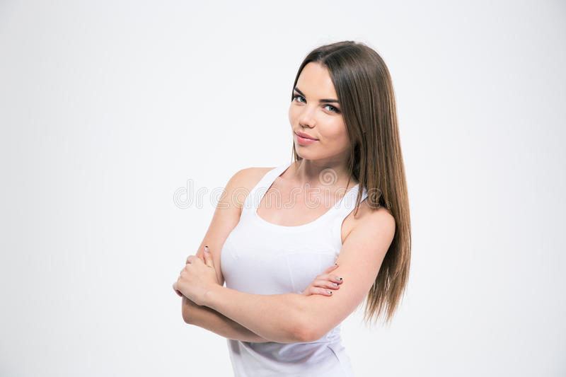 Girl standing with arms folded and looking at camera. Portrait of a happy cute girl standing with arms folded and looking at camera isolated on a white stock photography