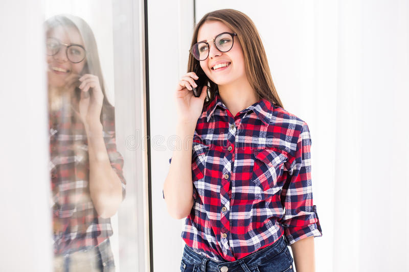 Girl standing on background of window, talking per mobile phone. stock photography