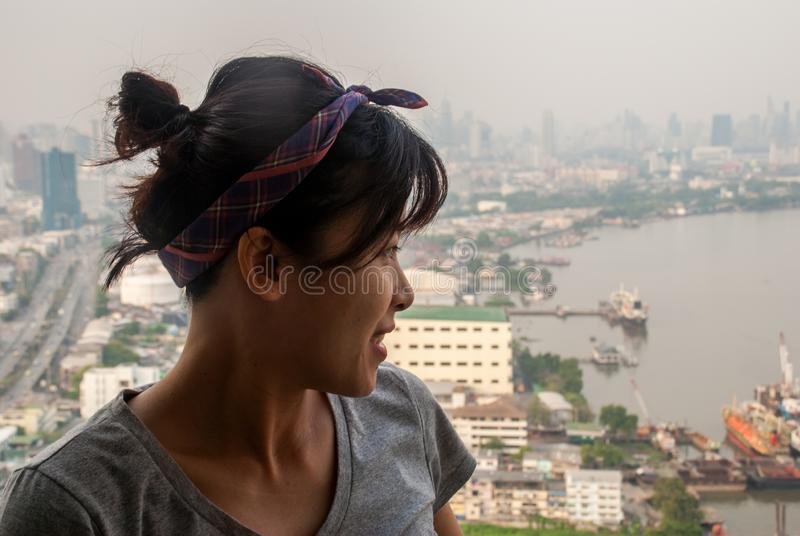 The girl standing on the balcony of the condominium Look at the river. The girl standing on the balcony of the condominium Looking at the Chao Phraya River royalty free stock image