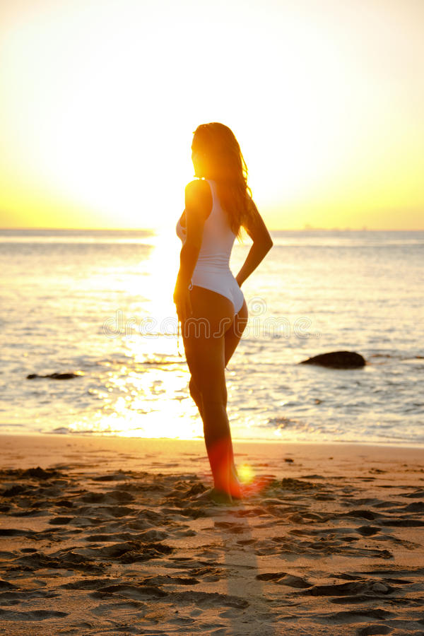 Girl standing on the beach in swimming suit during sunset stock images