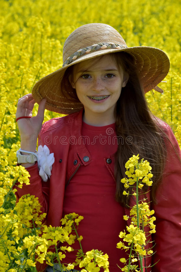 Girl standing in canola field stock photo