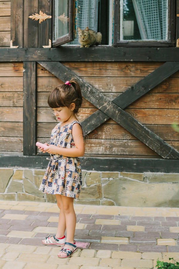 Girl standing with chalk near a wooden house stock photos