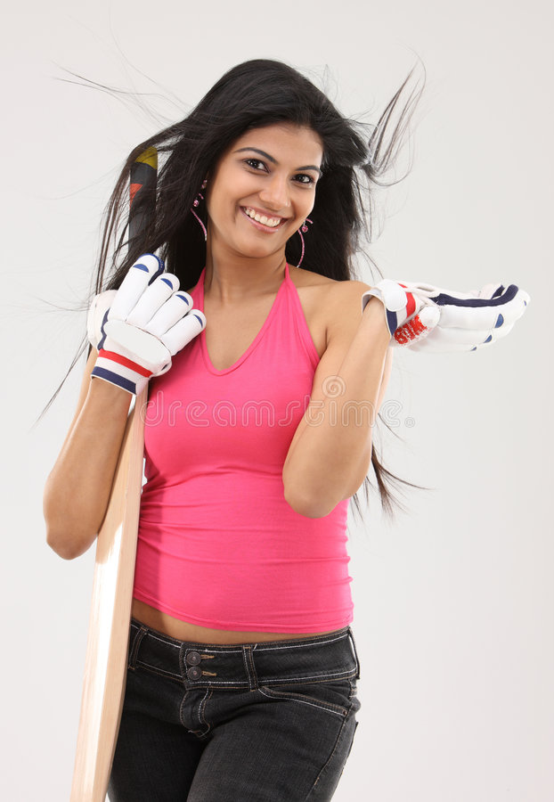 Girl standing with the cricket bat stock photo