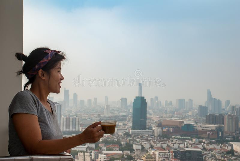 The girl standing drinking coffee on the balcony of the condominium looked at the river royalty free stock photo