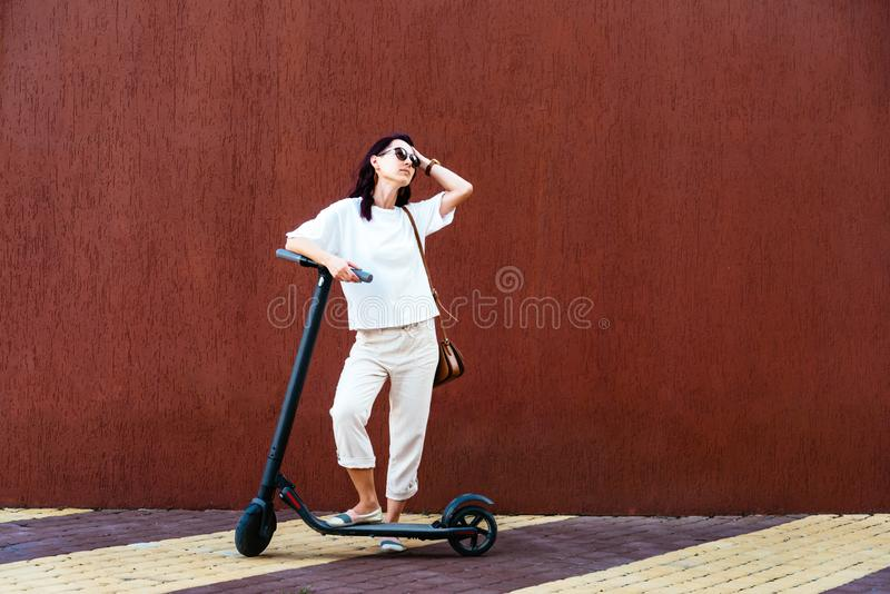 Girl standing with electric scooter near the wall in street. Modern girl in white clothes standing with electric scooter near the wall in street outdoor royalty free stock photos