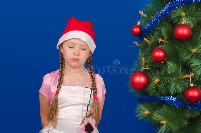 The girl standing at a fir-tree makes a wish. The little girl in a red cap standing at a fir-tree blindly Christmas makes a wish. New year stock images