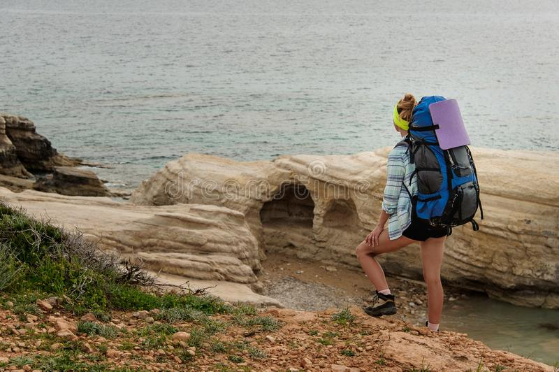 Girl standing with the foot on the rock holding hiking backpack looking at sea royalty free stock image