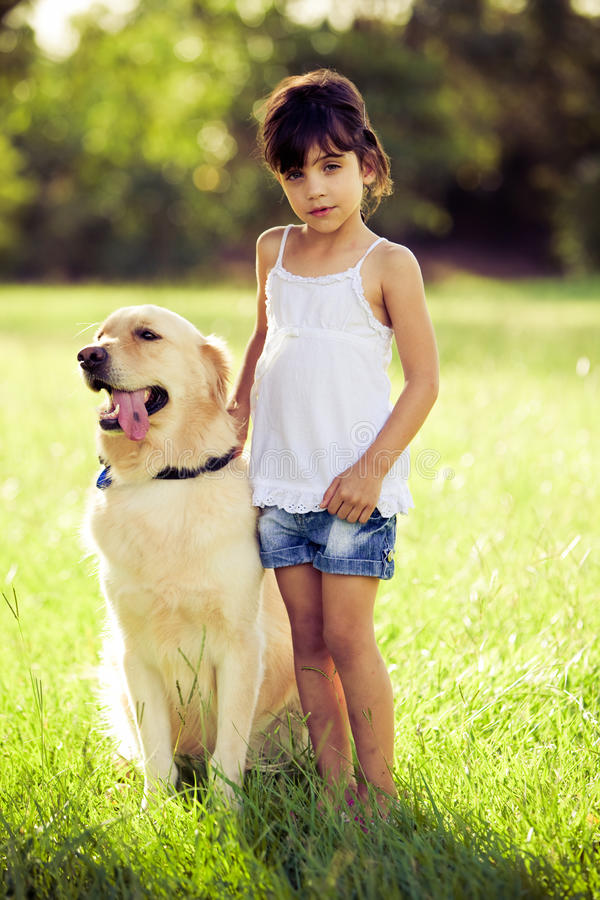 Download Girl Standing In Grass With Golden Retriever Stock Photo - Image: 13762288