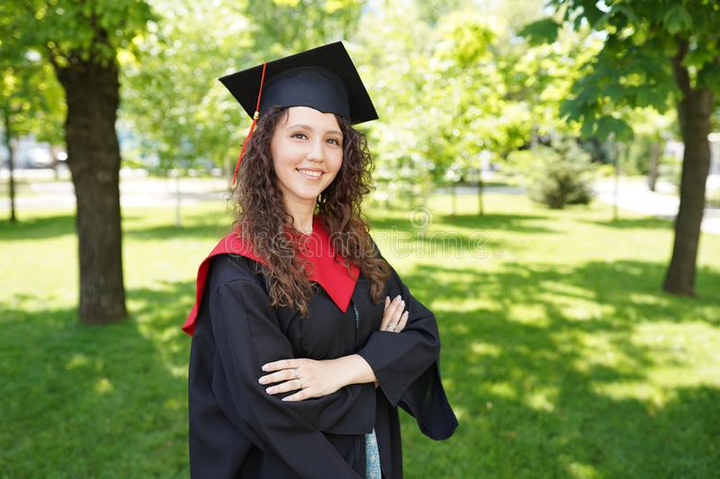 Girl is standing in green park near university. She is a graduate and in a good mood. copy space royalty free stock photo