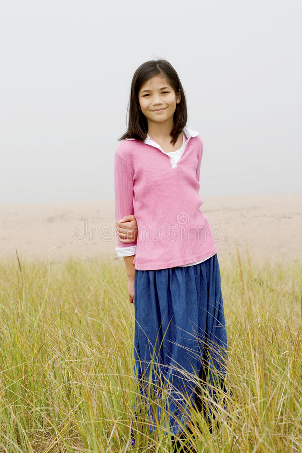 Free Girl Standing In Tall Grassy Field Royalty Free Stock Photo - 13402145