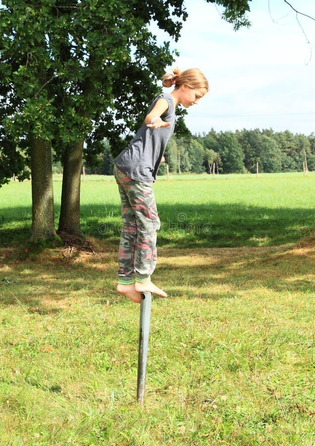 Girl standing on iron pillar. Barefoot kid - young smiling girl standing on metal pillar on meadow and keeping balance stock photo