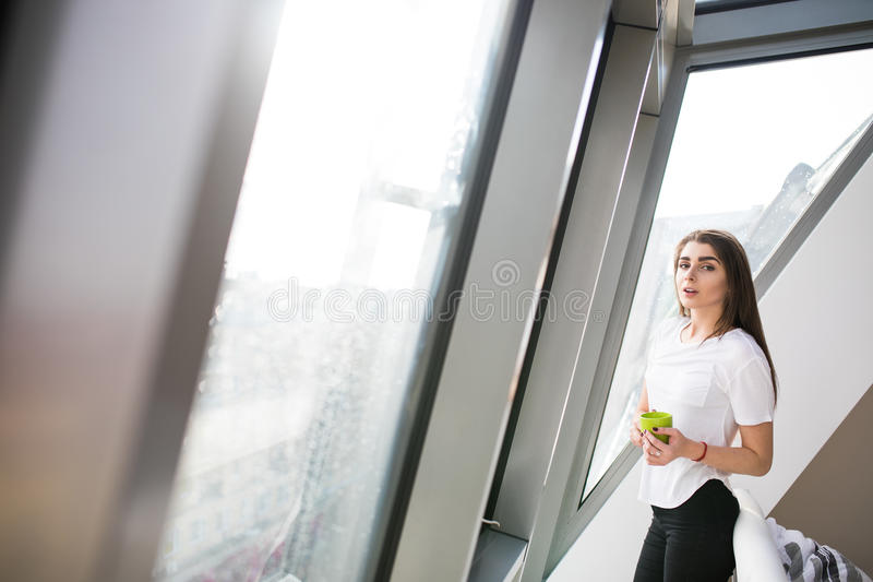 Girl standing near big window and drink coffee or tea in the morning at home stock photos