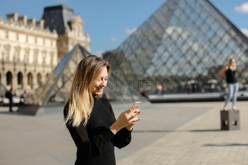 Girl standing near Louvre and glass pyramind in black dress in Paris, texting by smartphone. stock photos