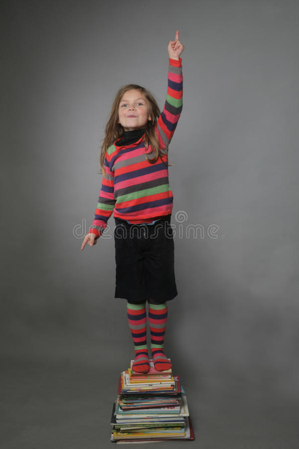 Free Girl Standing On Pile Of Books Royalty Free Stock Photography - 17139667