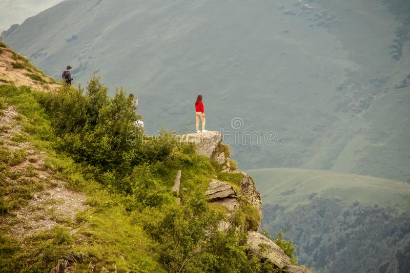 Girl standing on outcrop  looking over Devil`s Valley in the Caucasus Mountains of the Republic of Georgia with friends behind stock photography