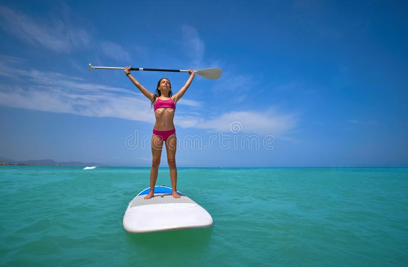 Girl standing on paddle surf board SUP. In summer stock photography