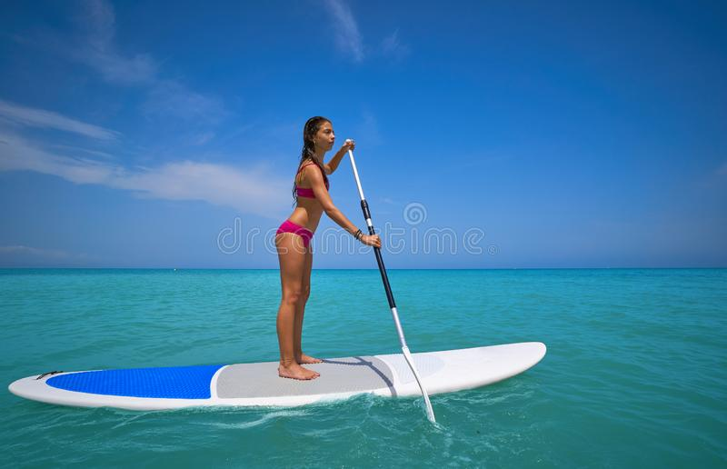 Girl standing on paddle surf board SUP. In summer stock photos