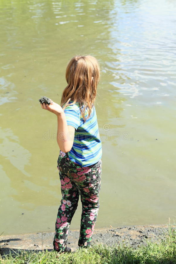 Girl standing by pond and throwing mud stock photos
