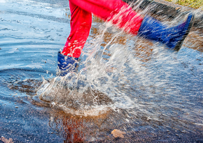 Girl standing in a puddle of water splashes. Girl in blue boots and red pants standing in a puddle of water splashes with fallen yellow leaves on autuman day stock images