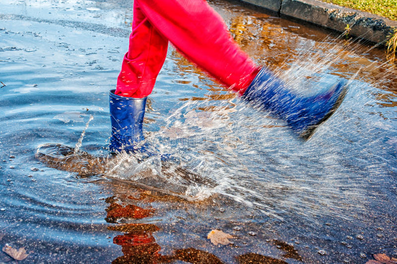 Girl standing in a puddle of water splashes. Girl in blue boots and red pants standing in a puddle of water splashes with fallen yellow leaves on autuman day royalty free stock photos