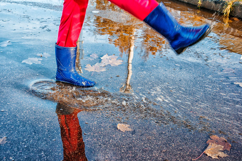Girl standing in a puddle of water splashes. Girl in blue boots and red pants standing in a puddle of water splashes with fallen yellow leaves on autuman day royalty free stock photo