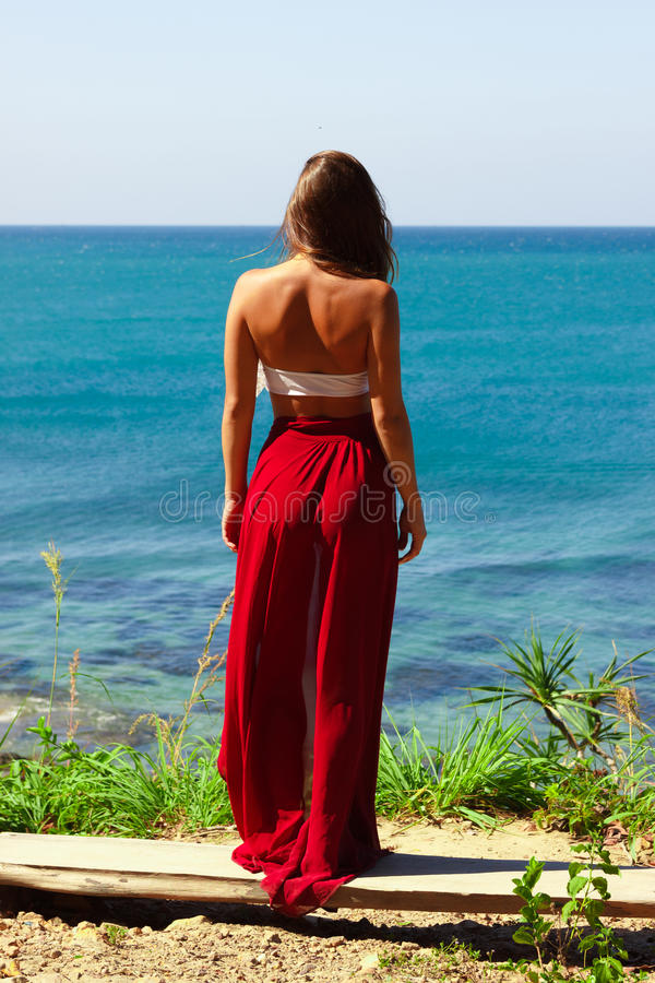 Girl standing in red skirt above the sea stock photo