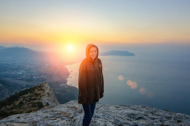 Girl standing on a rock in the rays of the rising sun, a journey.  royalty free stock images