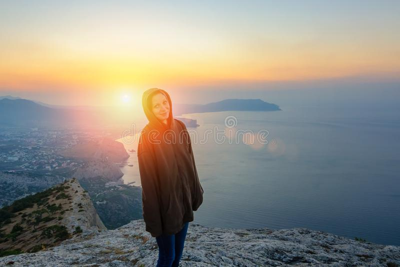 Girl standing on a rock in the rays of the rising sun, a journey.  royalty free stock photo