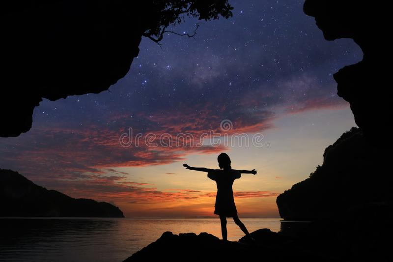 The girl standing on the rocks near the beach with beautiful million stars galaxy. And red sky sunset royalty free stock photography