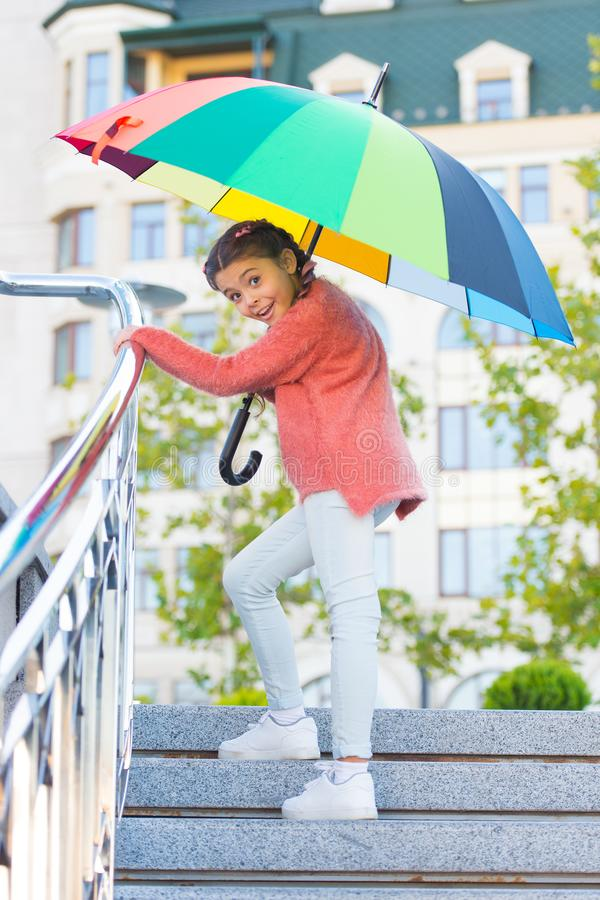 Girl standing on stairs and holding umbrella. Autumn rain. Waiting for bad weather under umbrella. Stylish girl in. Downtown. Positivity as resistance to cold royalty free stock photography
