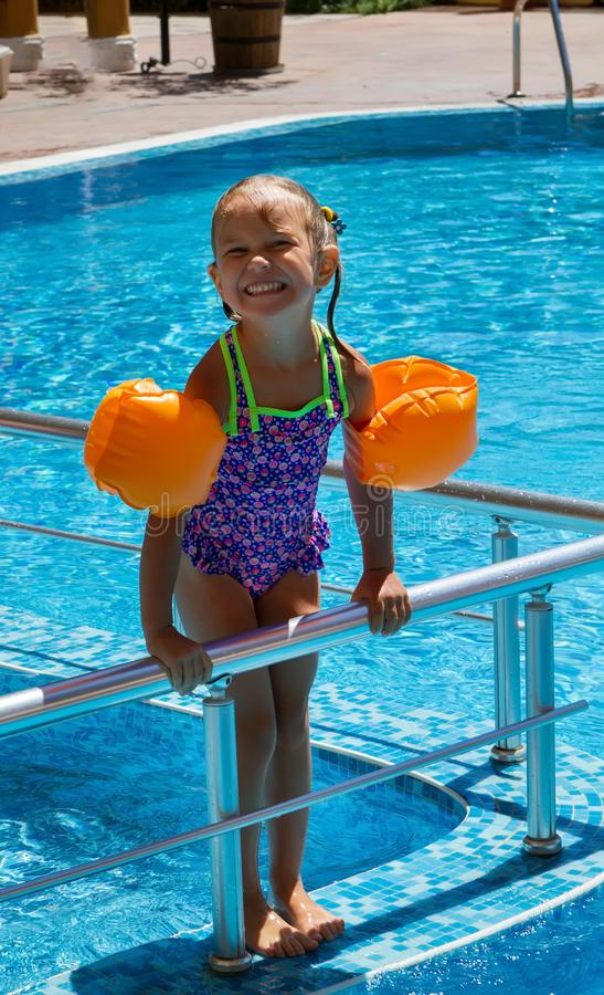 Girl standing on the steps of pool. royalty free stock image