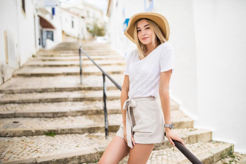 Young girl standing on the stone stairs and handrail at the street in summer stock photo